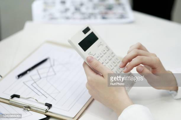 businesswoman using calculator in office - vermögensberatung stock-fotos und bilder