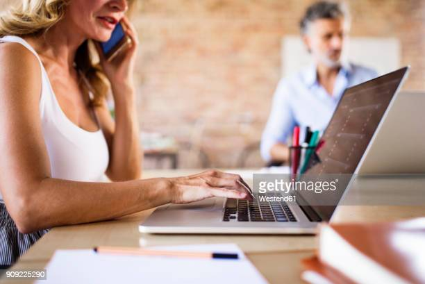 Businesswoman using cell phone and laptop at desk in office