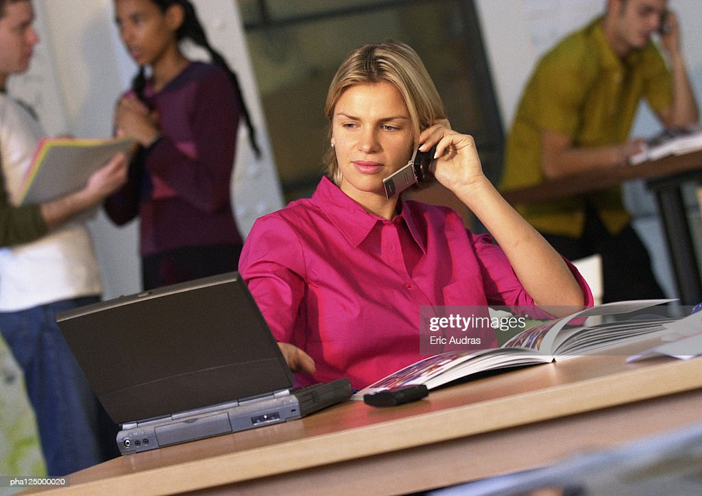 Businesswoman using cell phone and laptop computer : Stockfoto