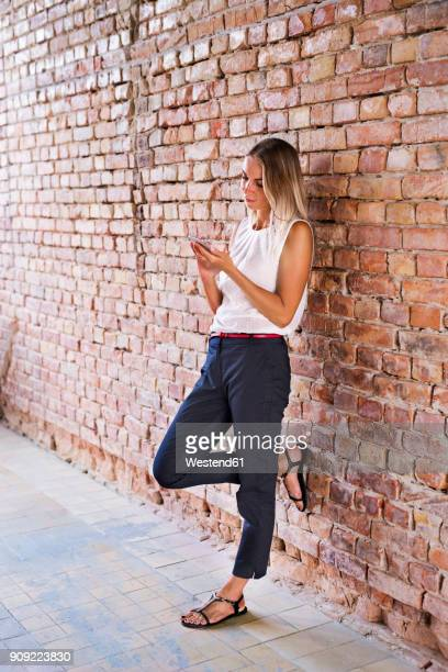 businesswoman using cell phone at brick wall - leaning stock pictures, royalty-free photos & images