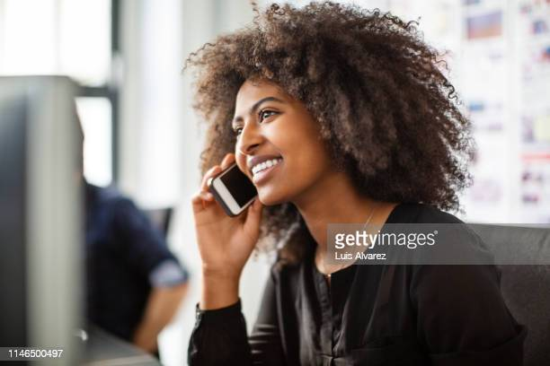businesswoman using cell phone at her desk - telefoon gebruiken stockfoto's en -beelden