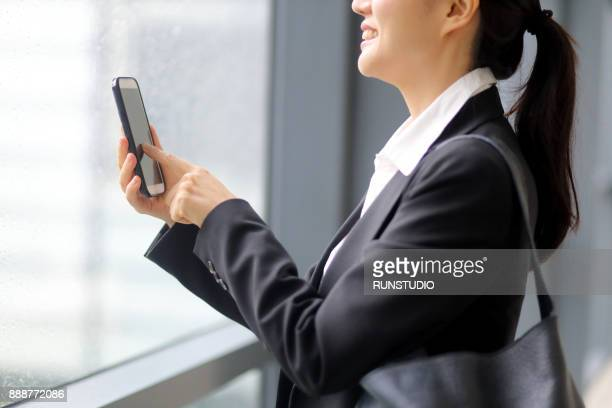 Businesswoman using cell phone at office window