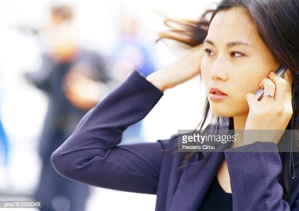 Businesswoman using cell phone, head and shoulders, close-up, blurred  background