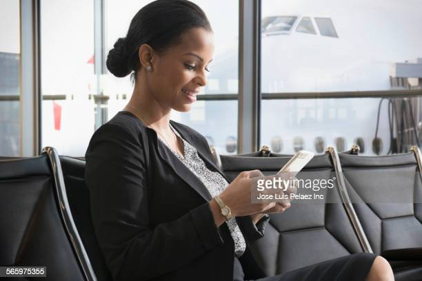 Businesswoman using cell phone in airport waiting area