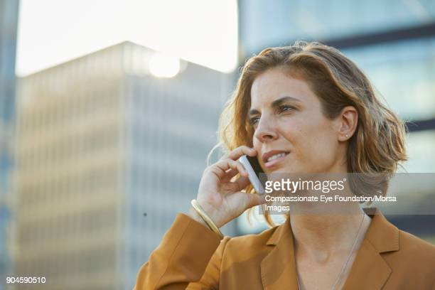 Businesswoman using cell phone in city