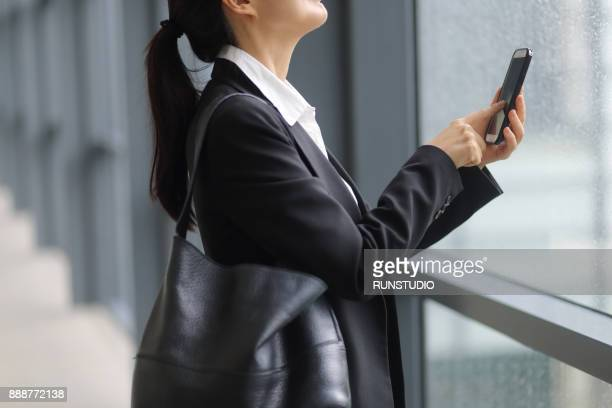 Businesswoman using cell phone in corridor