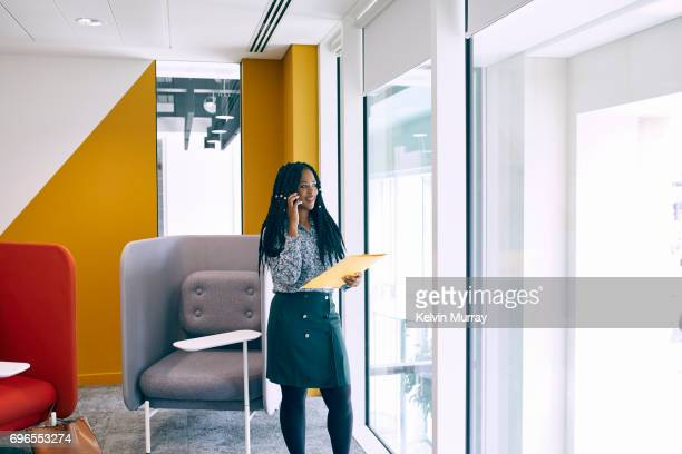 businesswoman using cell phone in creative office - black skirt stock pictures, royalty-free photos & images