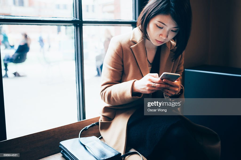 Businesswoman using cell phone in library : Stock Photo