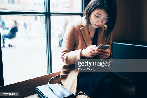 Businesswoman using cell phone in library