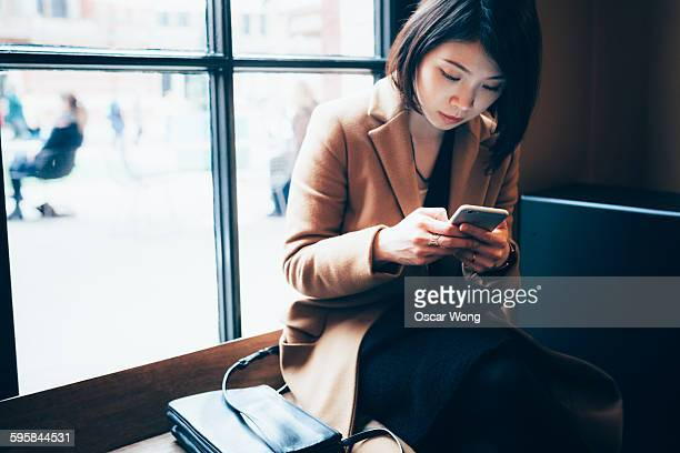 businesswoman using cell phone in library - leanincollection stock pictures, royalty-free photos & images