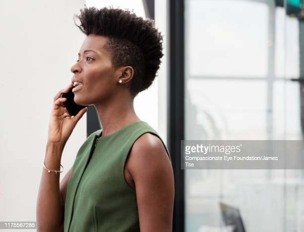 businesswoman using cell phone in modern office - vanguardians stock pictures, royalty-free photos & images