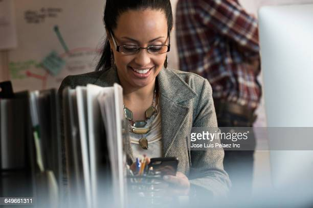 businesswoman using cell phone in office - black blazer stock photos and pictures