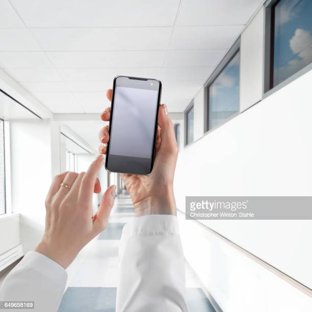 Businesswoman using cell phone in white corridor