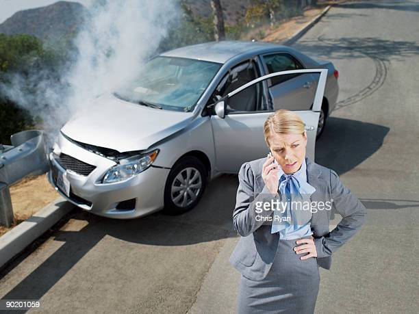Businesswoman using cell phone near car wrecked on guardrail