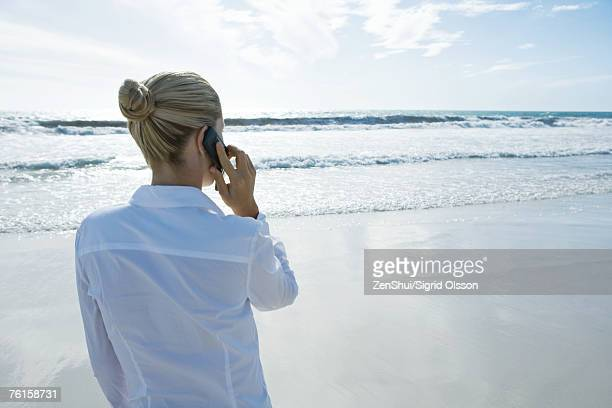 Businesswoman using cell phone on beach, rear view
