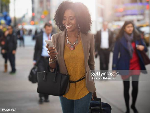businesswoman using cell phone on city sidewalk - handbag stock pictures, royalty-free photos & images