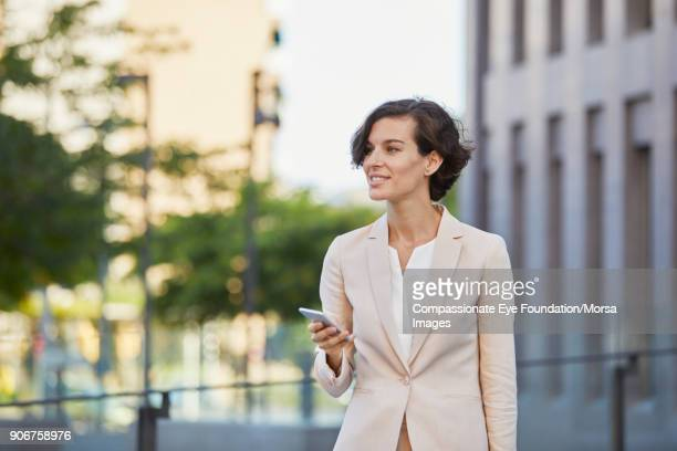 Businesswoman using cell phone on city street