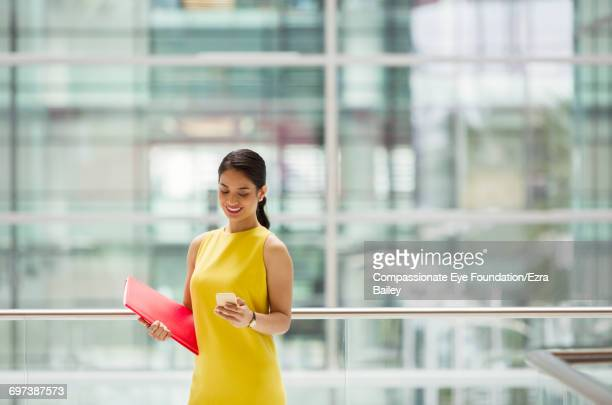 businesswoman using cell phone on office balcony - vestido amarillo fotografías e imágenes de stock
