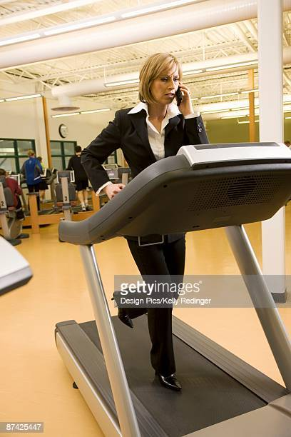 Businesswoman using cell phone on treadmill
