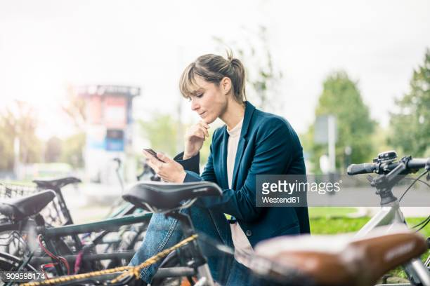 Businesswoman using cell phone outdoors surrounded by bicycles
