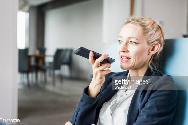 Businesswoman using cell phone sending voice mail
