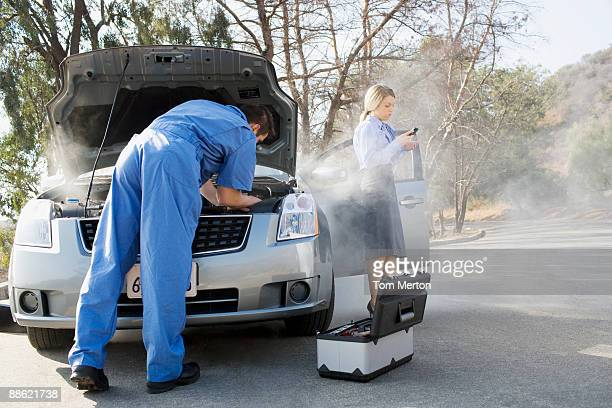 Businesswoman using cell phone while mechanic looks at car engine
