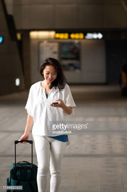 businesswoman using cellphone at subway station - wheeled luggage stock photos and pictures