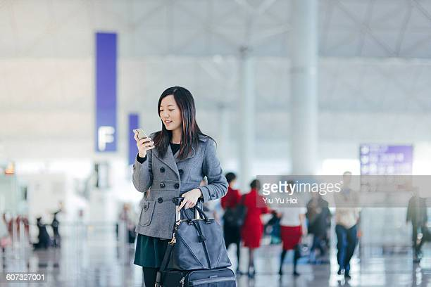 Businesswoman using cellphone in airport concourse