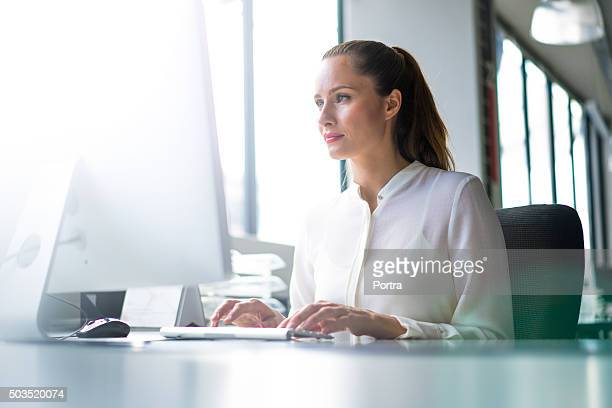 businesswoman using computer at desk in office - desktop pc stockfoto's en -beelden