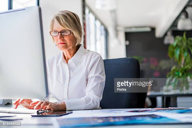 businesswoman using computer at desk in office - concentratie stockfoto's en -beelden