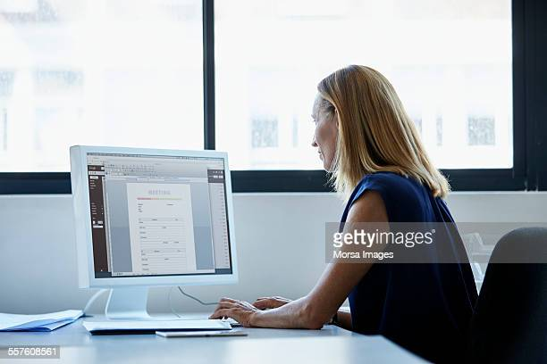 businesswoman using computer at desk - computermonitor stockfoto's en -beelden