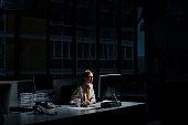 Businesswoman using computer in dark office