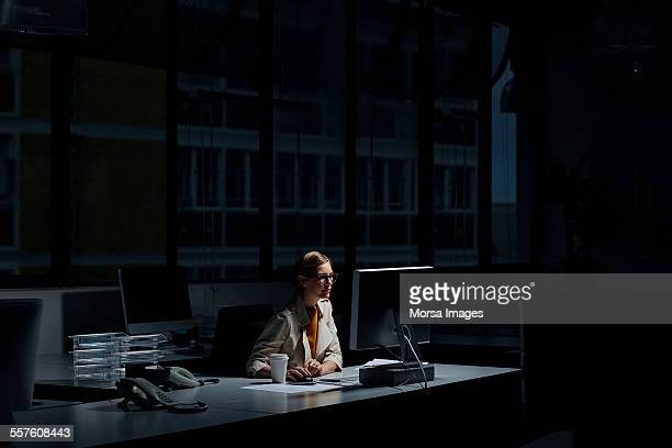businesswoman using computer in dark office - noche fotografías e imágenes de stock