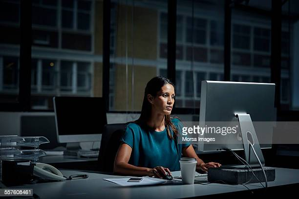 Businesswoman using computer in dark office