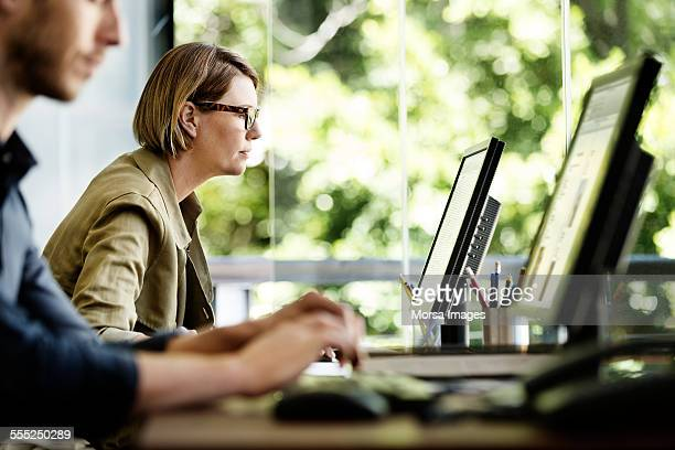 businesswoman using computer in office - desktop pc stockfoto's en -beelden