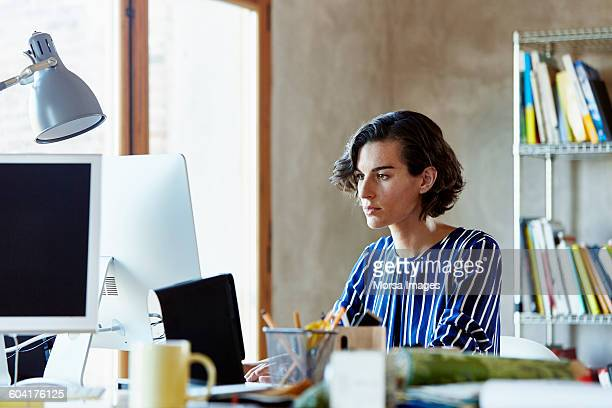 businesswoman using computer in office - leanincollection stock pictures, royalty-free photos & images