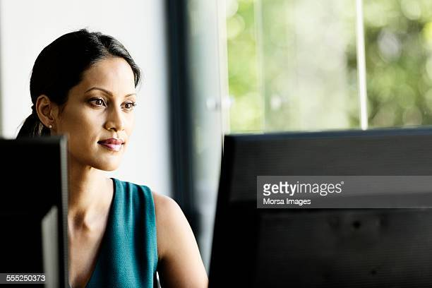 businesswoman using computer - looking stock pictures, royalty-free photos & images