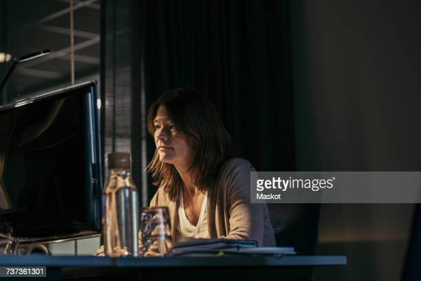 Businesswoman using computer while sitting at desk in office