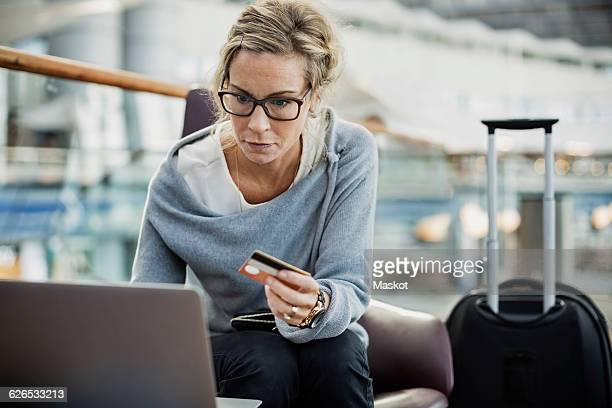 Businesswoman using credit card and laptop at airport lobby