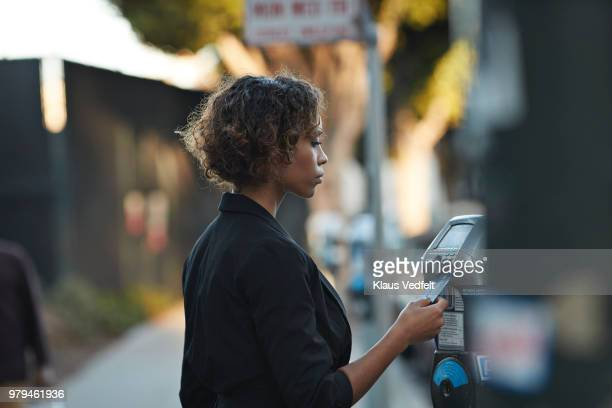 Businesswoman using credit card to pay for parking