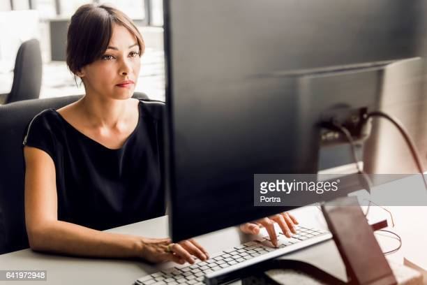 businesswoman using desktop pc at office - information equipment stock pictures, royalty-free photos & images