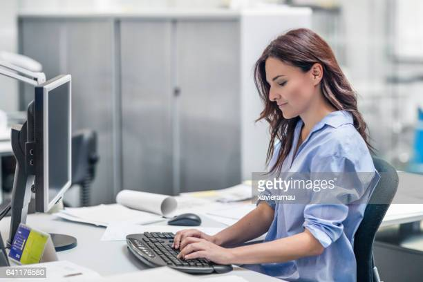 Businesswoman using desktop PC in office