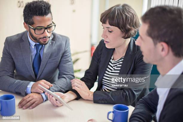 Businesswoman using digital PC with coworkers