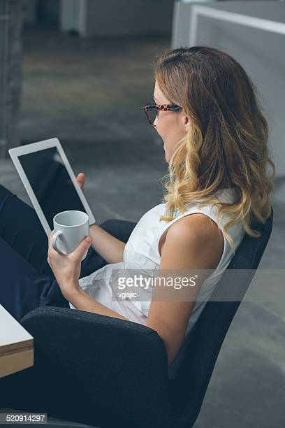 Businesswoman using digital tablet and drink coffee.
