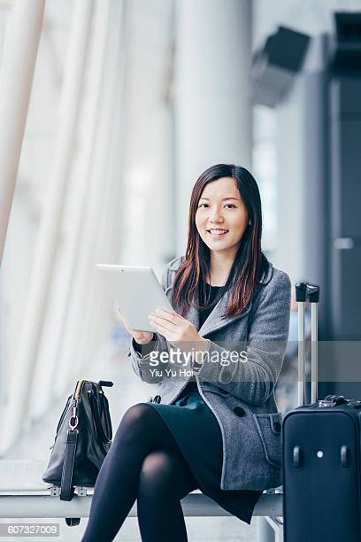 businesswoman using digital tablet at airport - yiu yu hoi stock pictures, royalty-free photos & images