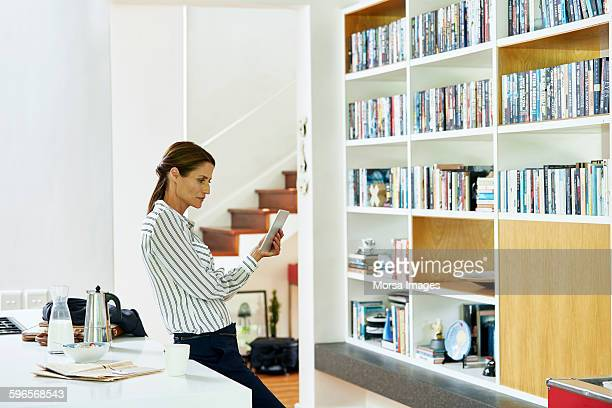 Businesswoman using digital tablet at home