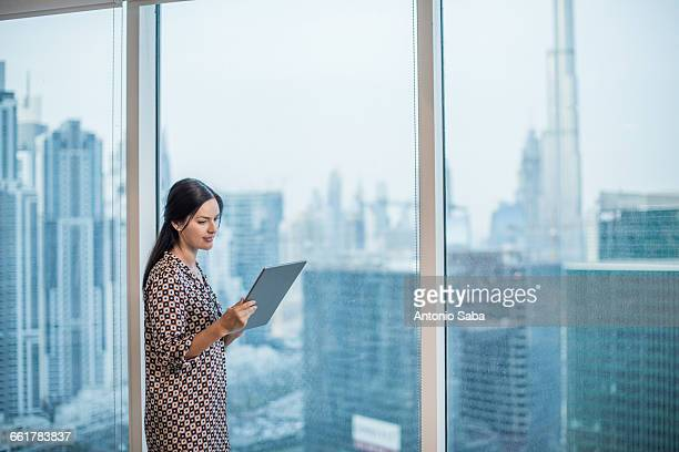 Businesswoman using digital tablet at window, Dubai, United Arab Emirates