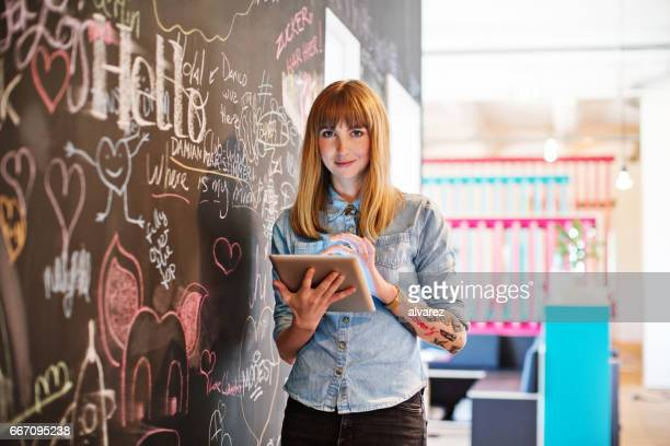 businesswoman using digital tablet by blackboard - hi tech moda stock pictures, royalty-free photos & images