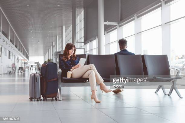Businesswoman using digital tablet in airport waiting area