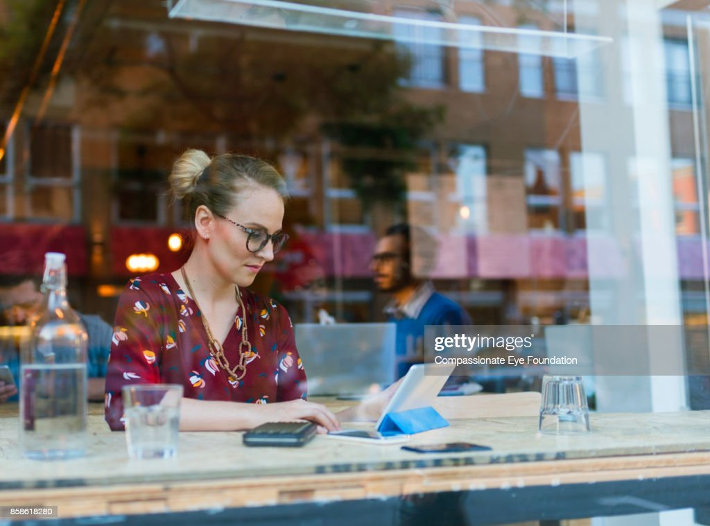 Businesswoman using digital tablet in cafe : Stock-Foto